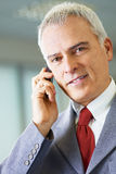 Mature businessman on the phone in office Royalty Free Stock Photography