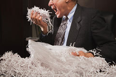 Mature businessman playing with paper shreddings Stock Images