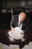 Mature businessman playing with paper shreddings Royalty Free Stock Photos