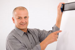 Mature businessman pointing at empty flip chart Stock Photography