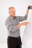 Mature businessman pointing at empty flip chart Stock Images