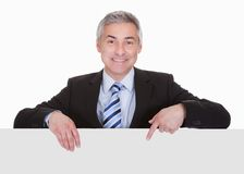 Mature businessman pointing at placard Stock Images