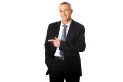 Mature businessman pointing to the left Stock Photos