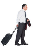 Mature businessman pulling his suitcase Royalty Free Stock Image
