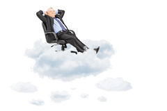 Mature businessman resting in armchair, floating on a cloud Royalty Free Stock Photo