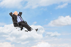 Mature businessman resting in armchair and floating on a cloud Royalty Free Stock Image