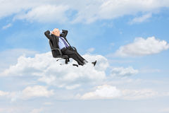Mature businessman resting in armchair and floating on a cloud Stock Photography
