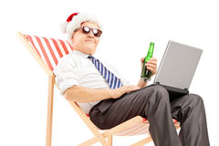 Mature businessman with santa hat on a chair, drinking beer and Royalty Free Stock Photography