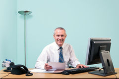 Mature businessman sat at his office desk Stock Photos
