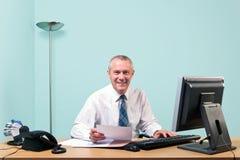 Mature businessman sat at his office desk Stock Photos