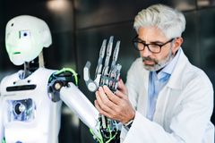 Mature businessman or scientist with a robot. Royalty Free Stock Image
