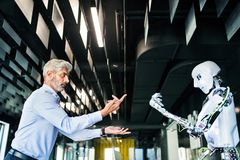 Mature businessman or a scientist with robot. Stock Photos