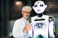 Mature businessman or a scientist with robot. Royalty Free Stock Photography