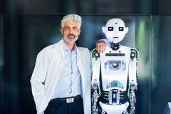 Mature businessman or a scientist with robot. Royalty Free Stock Photo