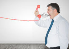 Mature businessman screaming on the phone. In an empty room Stock Photo