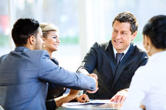 Mature businessman shaking hands to seal Royalty Free Stock Image