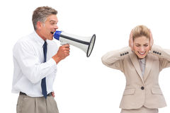 Mature businessman shouting at his coworker with megaphone Stock Photo