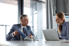 Mature businessman showing documents to female colleague at conference table Royalty Free Stock Photography