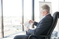 Businessman looking at diagrams Stock Photo