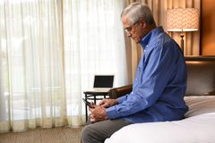 Mature Businessman sitting on the bed in his hotel room royalty free stock image