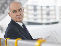 Mature Businessman Sitting On Bench With Newspaper. Portrait of a mature businessman sitting on bench with newspaper and looking away Royalty Free Stock Photography