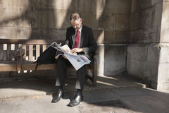 Mature businessman sitting on bench reading newspaper Stock Photos