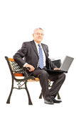 Mature businessman sitting on a bench and working on a laptop Royalty Free Stock Image