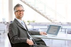 Mature businessman sitting at office desk royalty free stock photos