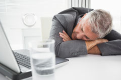 Mature businessman sleeping on desk Royalty Free Stock Images