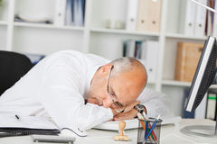 Mature Businessman Sleeping On Desk Stock Image