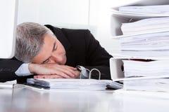 Mature businessman sleeping at desk. Tired Mature Businessman Sleeping At Desk In Office Royalty Free Stock Photo