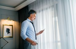 Mature businessman with smartphone in a hotel room. Stock Photography