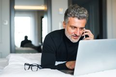 Mature businessman with smartphone in a hotel room. stock images