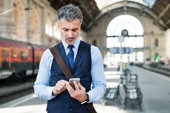 Mature businessman with smartphone on a train station. Stock Photo