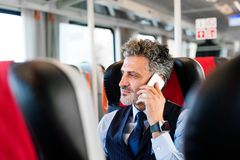 Mature businessman with smartphone travelling by train. Handsome mature businessman travelling by train. A man with smartphone, making a phone call Stock Photos