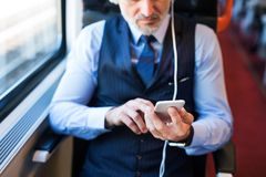 Mature businessman with smartphone travelling by train. Unrecognizable mature businessman travelling by train. A man with smartphone and headphones, listening Royalty Free Stock Images