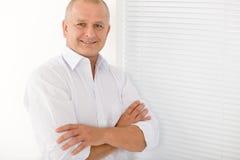 Mature businessman smile cross arms posing Stock Photos