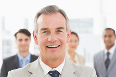 Mature businessman smiling at camera with team behind him Royalty Free Stock Images