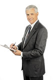 Mature Businessman Smiling With Clipboard Royalty Free Stock Images
