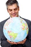 Mature businessman smiling at global. Business expansion against a white background royalty free stock images