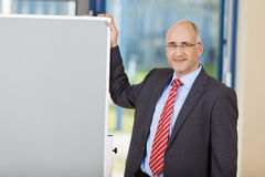 Mature Businessman Standing By Flipchart Royalty Free Stock Images