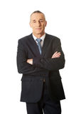 Mature businessman standing with folded arms Stock Image
