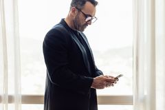 Mature businessman standing in hotel room using his cell phone. CEO on business trip texting on mobile phone in hotel room stock images