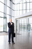 A mature businessman standing in the lobby of a modern office building, adjusting his tie Royalty Free Stock Photography