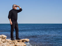 Mature businessman standing lookout on a rock. A Mature middle-aged Business man standing lookout on a rock above a calm blue ocean with his hand raised to his Royalty Free Stock Photo