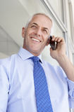 Mature Businessman Standing Outside Modern Office Talking On Phone Royalty Free Stock Photography