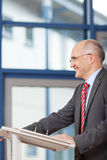 Mature Businessman Standing At Podium Stock Photo
