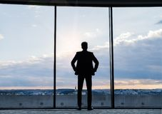 Mature businessman standing at the window in a hotel. Royalty Free Stock Photos
