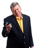 Mature businessman staring at cell phone, isolated. Portrait of mature businessman staring at cell phone with troubled look on face, isolated on white Royalty Free Stock Image