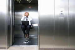 Mature businessman on stool in lift, laptop on lap, head in hands Royalty Free Stock Images